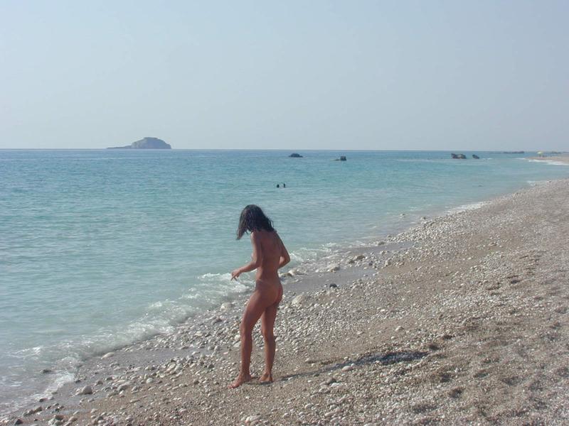 Стройная брюнетка гуляет на нудистском пляже 13 фото