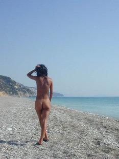 Стройная брюнетка гуляет на нудистском пляже