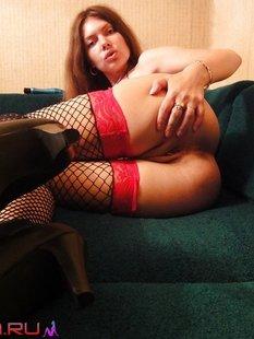 Телка в чулках с большими сиськами лежит на диване, раздвинув ноги