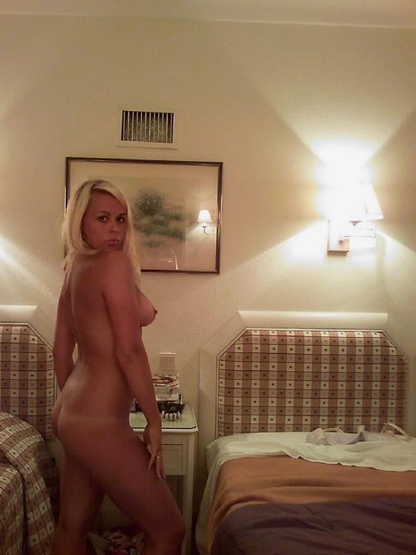 Попастая блондинка сняла белую майку и показывает киску на кровати 15 фото