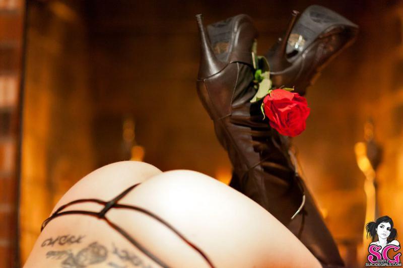 Брюнетка в длинных сапогах снимается у камина с топором и розой 12 фото