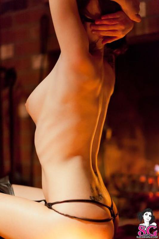 Брюнетка в длинных сапогах снимается у камина с топором и розой 30 фото