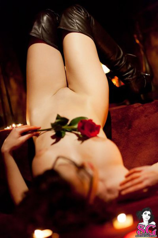 Брюнетка в длинных сапогах снимается у камина с топором и розой 16 фото