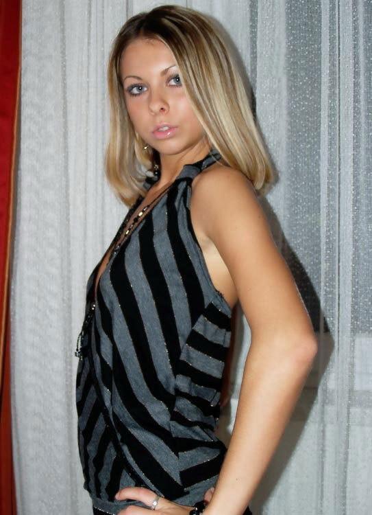 Милая блондинка показывает упругие сиси возле занавесок 1 фото