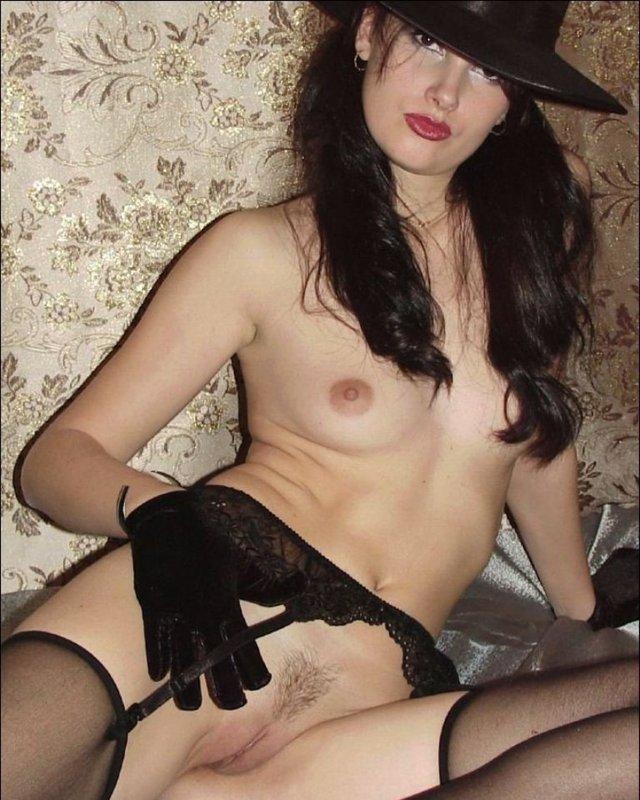 Жгучая брюнетка в шляпе и перчатках светит голым телом на кровати 3 фото