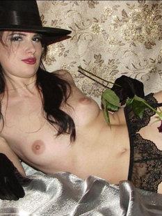 Жгучая брюнетка в шляпе и перчатках светит голым телом на кровати