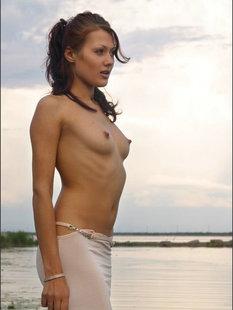Голая брюнетка нежно позирует на берегу реки