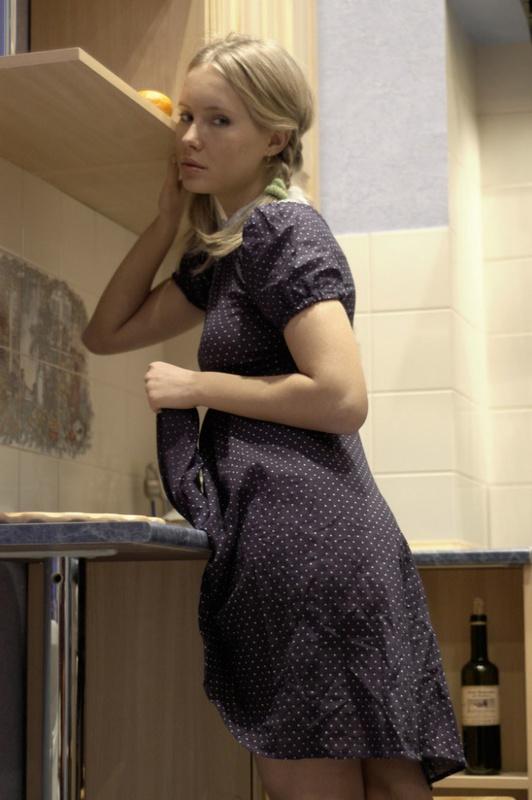 Молодая блондинка с косичками позирует на кухне 6 фото