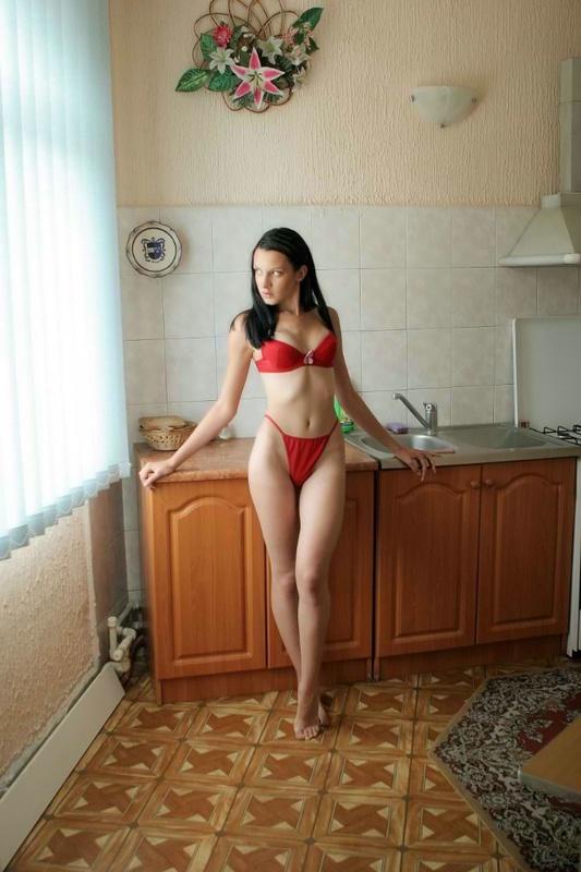 Худая брюнетка в красном белье позирует на кухне 2 фото