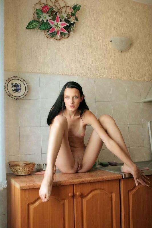 Худая брюнетка в красном белье позирует на кухне 9 фото