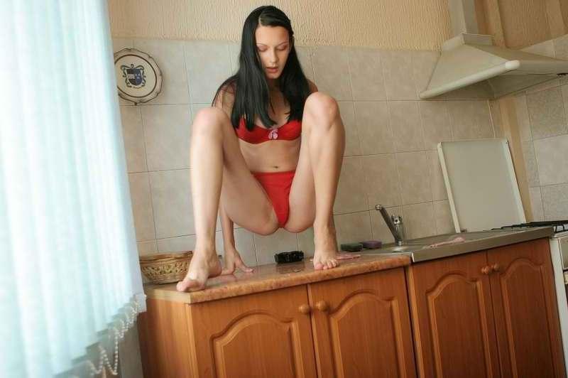 Худая брюнетка в красном белье позирует на кухне 5 фото