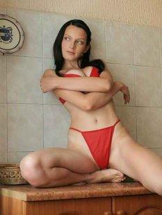 Худая брюнетка в красном белье позирует на кухне
