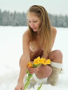 18летняя девушка в сапогах позирует на снегу с тюльпанами голая
