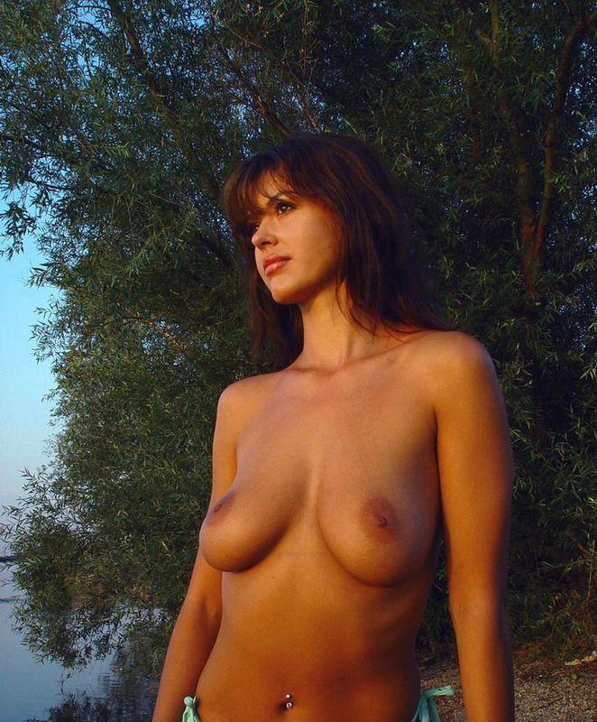 Грудастая мамка в синем бикини позирует на берегу реки 7 фото