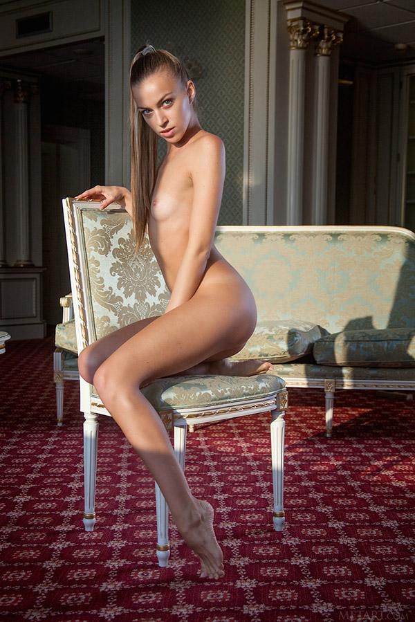 Стройная девушка разделась и выгибает поясницу на стуле и ковре 5 фото