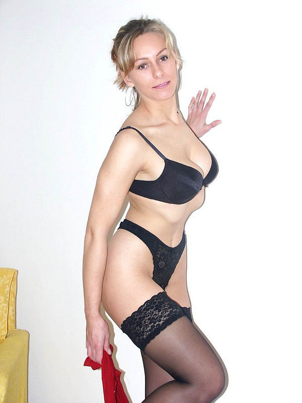 Женщина позирует на камеру в чулках и нижнем белье 3 фото