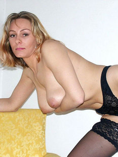 Женщина позирует на камеру в чулках и нижнем белье