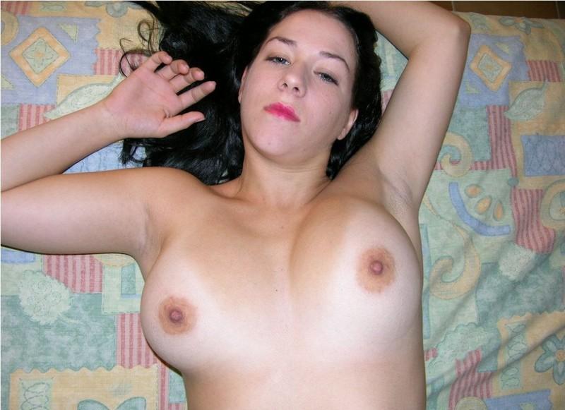 Брюнетка с татуировкой на животе разлеглась на кровати 3 фото