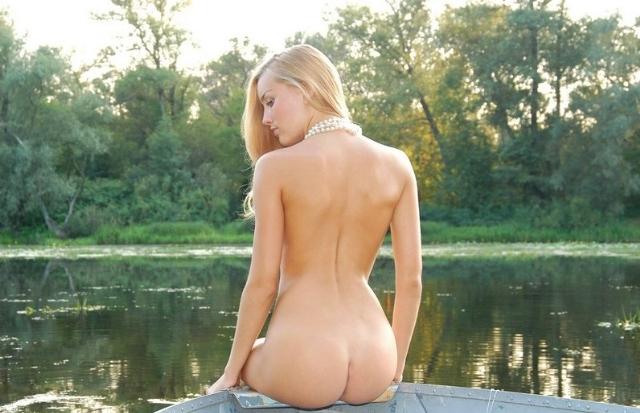 Голая славяночка плавает в лодке на речке 9 фото