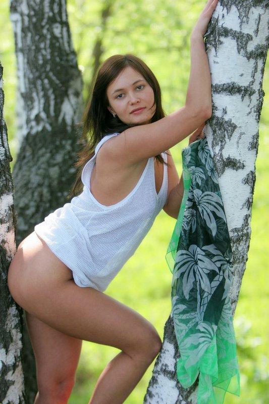 Молодая брюнетка разделась на природе возле дерева 2 фото