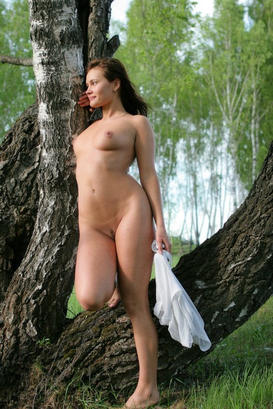 Молодая брюнетка разделась на природе возле дерева 10 фото