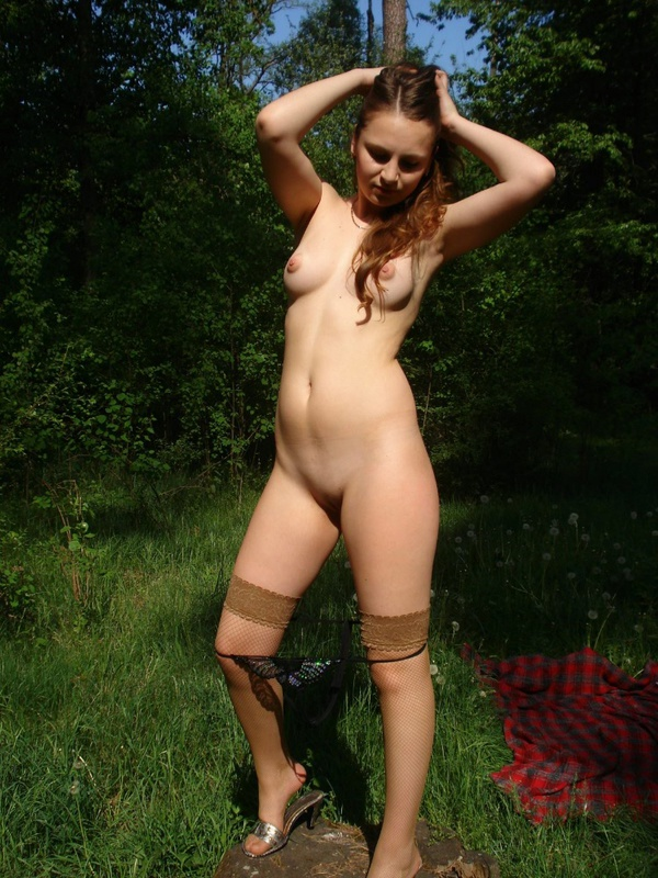 Молодая девка в чулках позирует голая на природе 4 фото