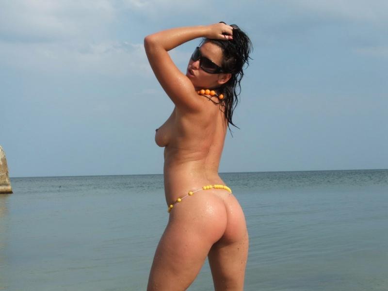 Грудастая модель позирует голой на берегу моря 9 фото