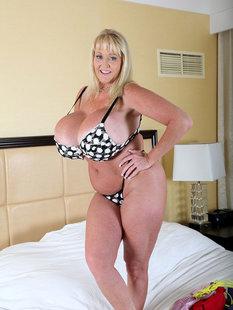 Веселая баба с огромными сиськами в спальне на постели