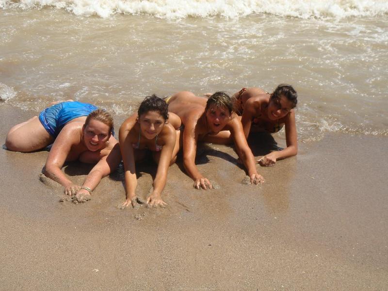 Туристки снимают лифчики на пляже и мажут голые тела песком 5 фото