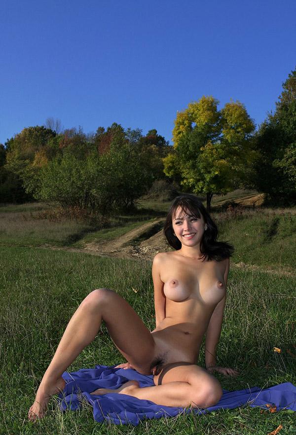 Сисястая брюнетка позирует голая на синем покрывале и у дерева 9 фото