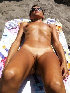 Обнаженная девушка загорает на берегу моря
