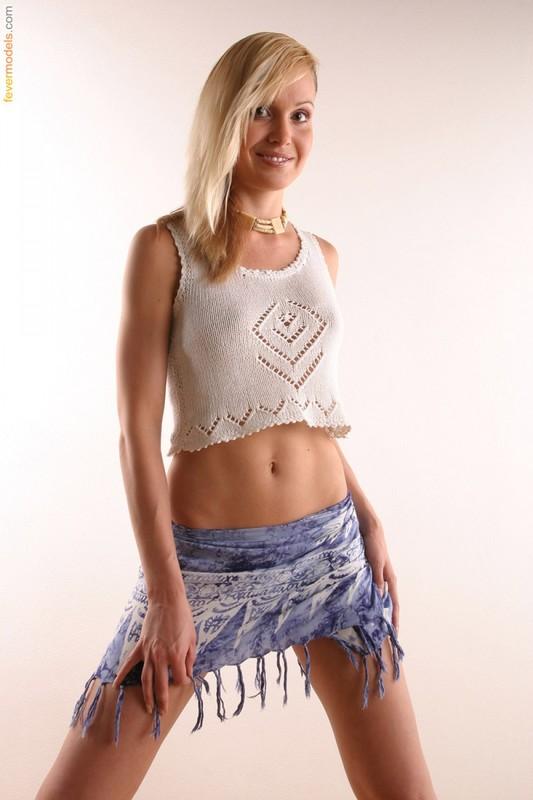 Блондинка в вязанной майке позирует у стены и раскрывает киску на полу 2 фото
