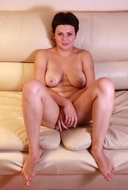 Брюнетка с кроткой стрижкой позирует у табуретки и на диване 9 фото