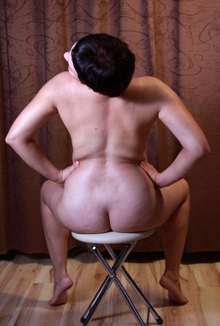 Брюнетка с кроткой стрижкой позирует у табуретки и на диване 1 фото