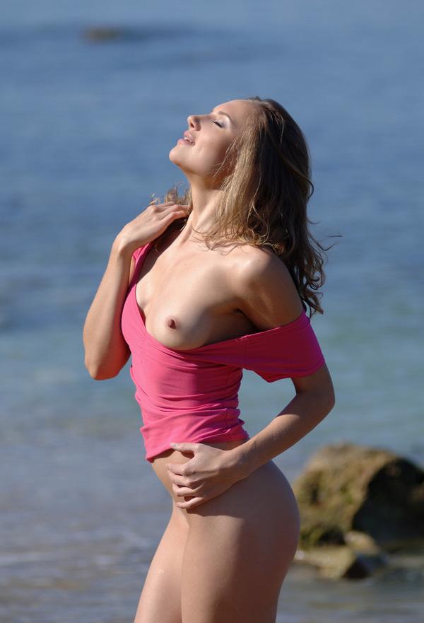 Молодая девка позирует без одежды в воде на пляже 4 фото