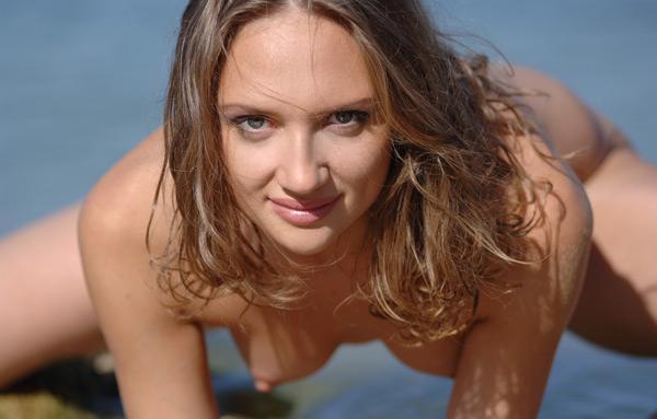 Молодая девка позирует без одежды в воде на пляже 14 фото