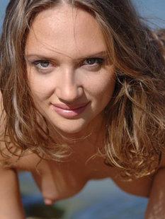 Молодая девка позирует без одежды в воде на пляже