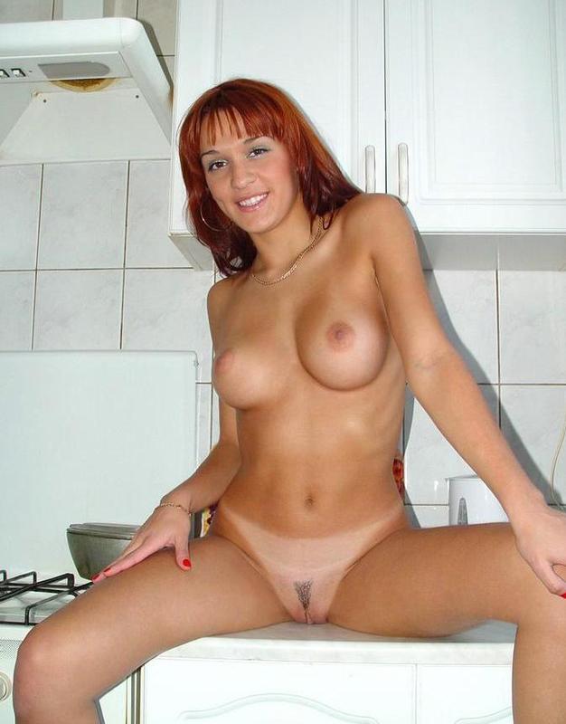 Рыжая девушка позирует и раздевается на кухне 11 фото