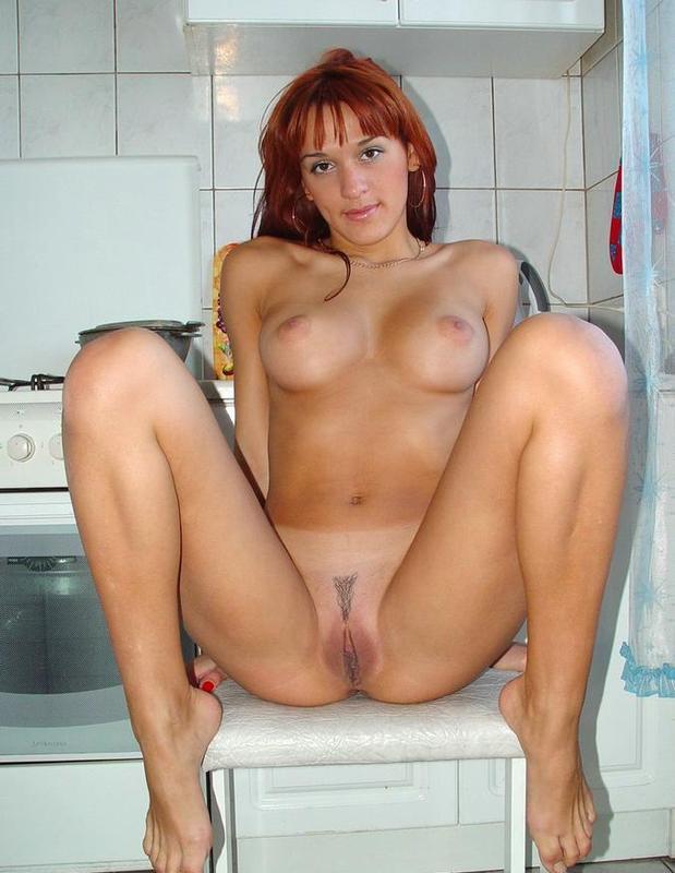 Рыжая девушка позирует и раздевается на кухне 13 фото