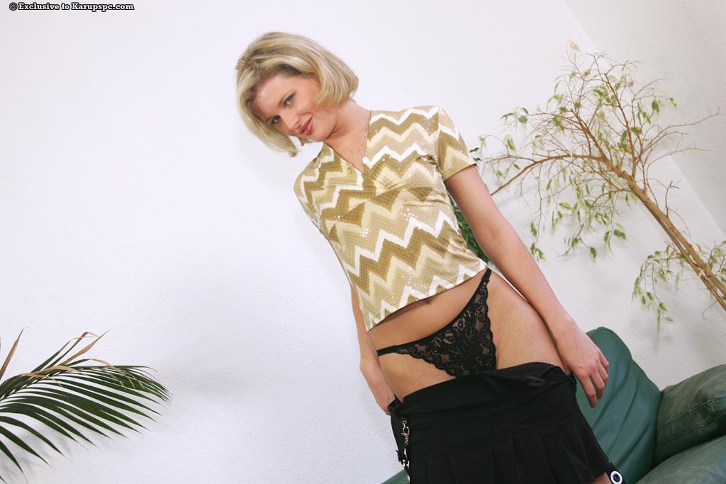 Длинноногая блондинка Laura раздевается на зелёном диване 3 фото