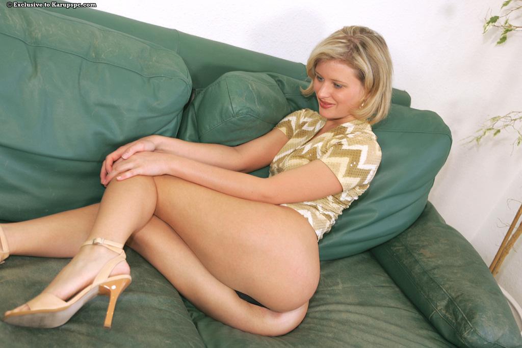 Длинноногая блондинка Laura раздевается на зелёном диване 4 фото