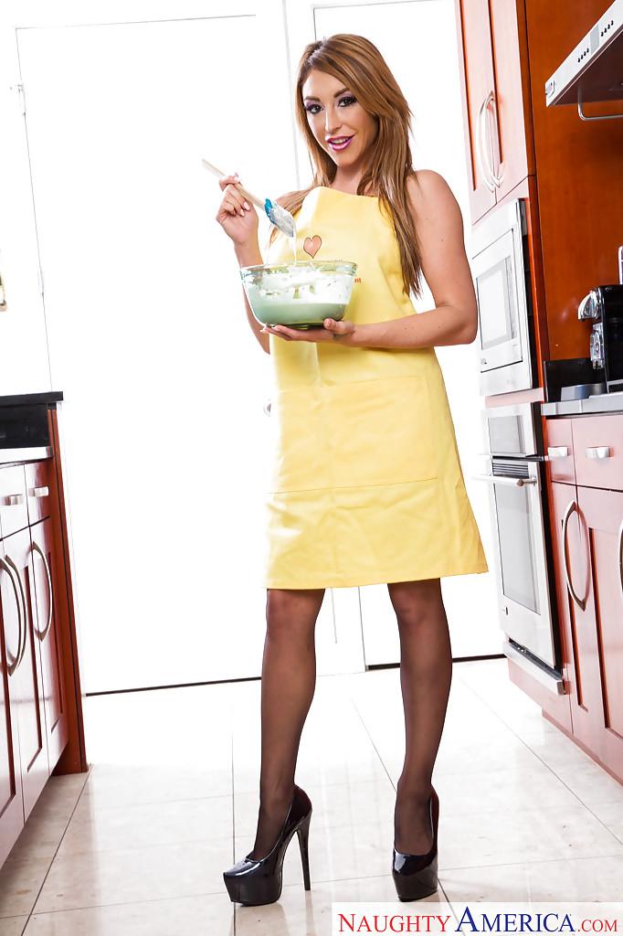 Домохозяйка позирует на кухне в фартуке и черных чулках 1 фото