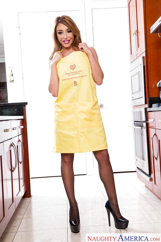 Домохозяйка позирует на кухне в фартуке и черных чулках 4 фото