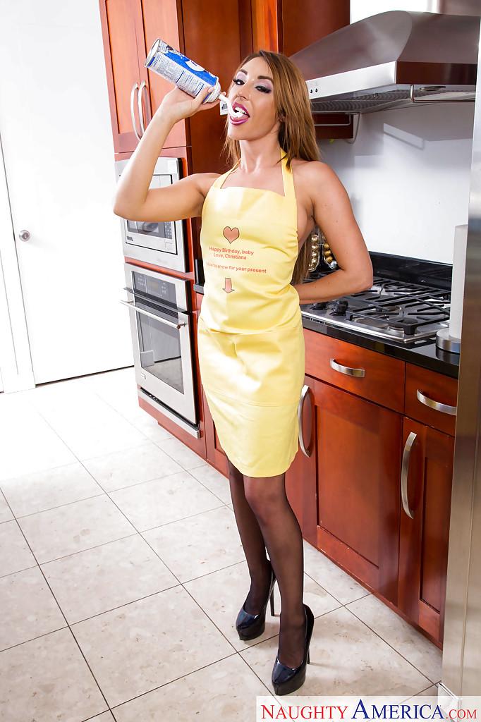 Домохозяйка позирует на кухне в фартуке и черных чулках 8 фото