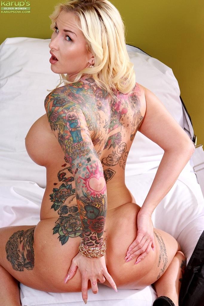 Зрелая татуированная блондинка оголяет большие сиськи и задницу перед мастурбацией 9 фото