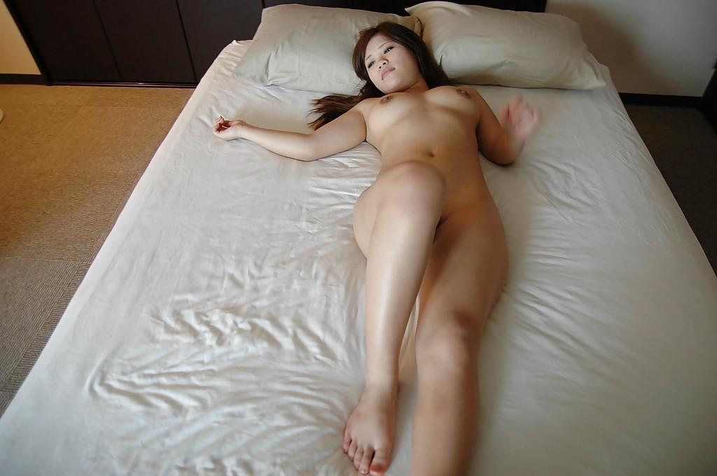 Молодая азиатка раздевается и позирует голой на кровати 16 фото
