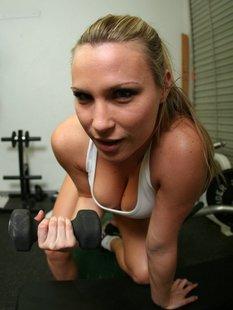 Спортивная милашка раздевается и позирует в боксерских перчатках в спортзал ...