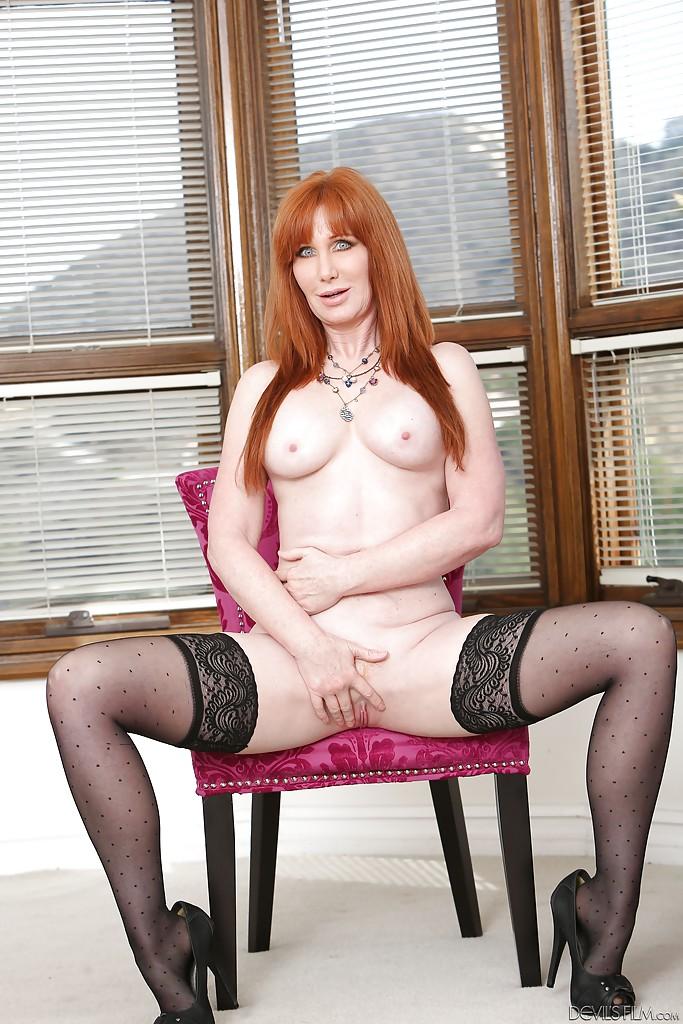 Рыжая мамаша в чёрных чулках мастурбирует на стуле и полу 13 фото