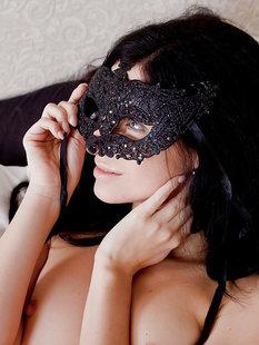Длинноволосая брюнетка разделась в спальне и примеряет маску