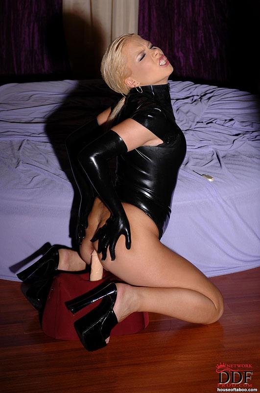 Блондинка в латексе и чулках мастурбирует на сумке с фаллосом 15 фото